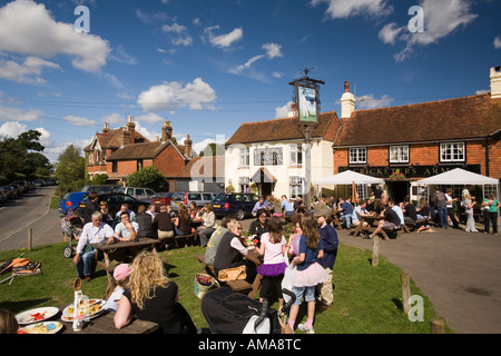 UK West Sussex Wisborough Green drinkers outside The Cricketers Village Pub in sunshine - Stock Photo