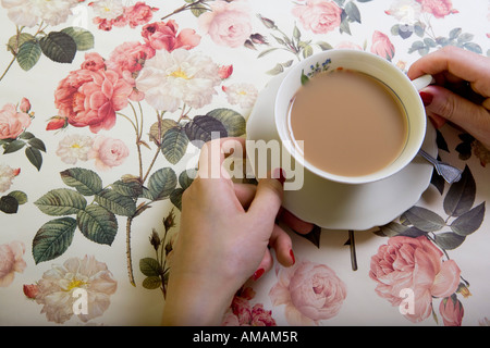 A cup of tea on a floral tablecloth - Stock Photo