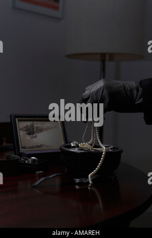 Detail of a thief with a handful of jewelry - Stock Photo