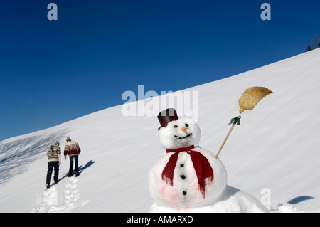 Snow man, couple in background - Stock Photo