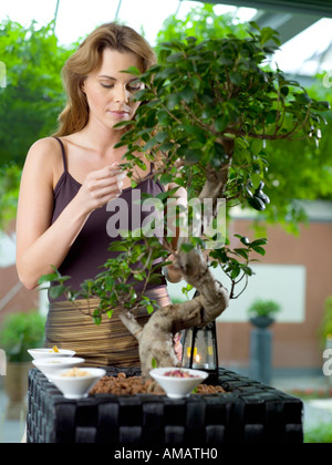Woman with spice in bowl by plant - Stock Photo