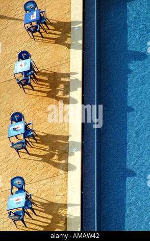 tables and  chairs seats set out alongside a swimming pool - Stock Photo