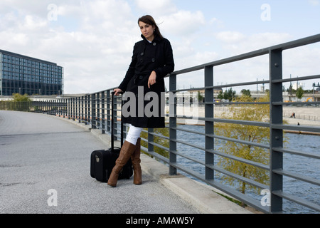 A woman standing on a bridge over a river with luggage - Stock Photo