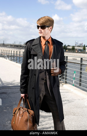A businessman walking across a bridge - Stock Photo