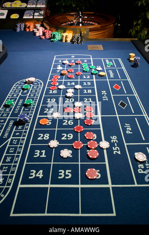 Roulette Table and Wheel with bets placed - Stock Photo