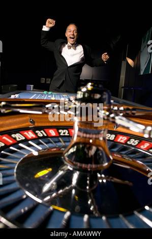 Roulette wheel with ecstatic man jumping - Stock Photo
