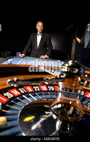 Well dressed man playing roulette in casino - Stock Photo