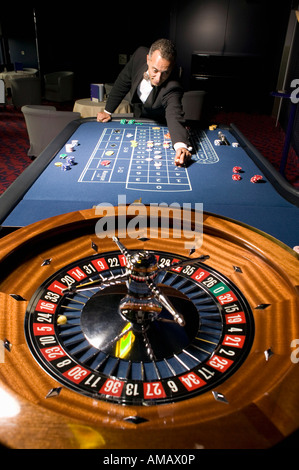 Euro Casino. Man placing bet on roulette table - Stock Photo