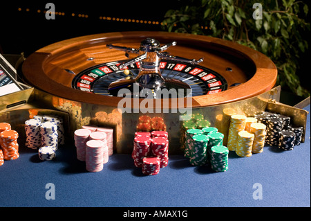 Roulette wheel with multiple stacks of gambling chips - Stock Photo
