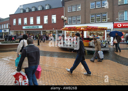 Chelmsford high street outdoor shopping precinct on wet rainy day busy with shoppers kiddies roundabout ride and - Stock Photo