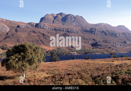 Slioch towering above Loch Maree in Scotland on a sunny autumn day - Stock Photo