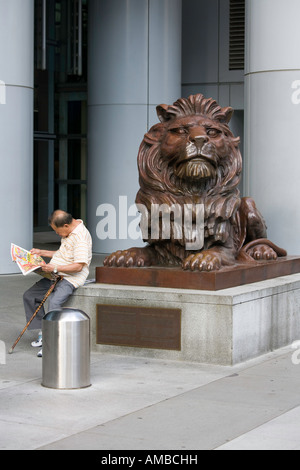 A man reads his newspaper by one of the bronze lion statues in front of the HSBC headquarters in Hong Kong. - Stock Photo
