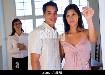portrait of young hispanic couple at home holding their house keys - Stock Photo
