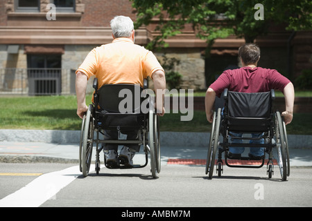 Rear view of a middle-aged man and a middle-aged woman crossing a road in wheelchairs - Stock Photo