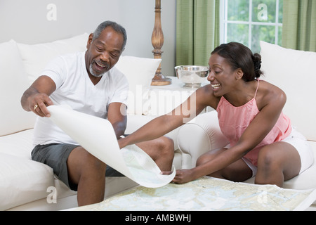 Middle-aged couple sitting on a couch and studying a map of sailboat racing