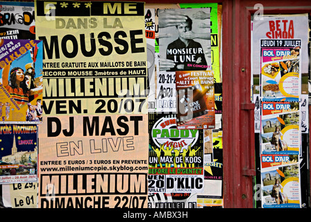 posters stuck up on a wall in limoux france advertising club nights and concerts - Stock Photo
