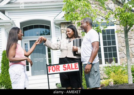Real estate agent giving key to a middle-aged woman in front of a house and smiling - Stock Photo