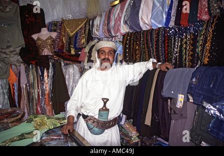 Yemeni fabric seller chewing qat in his shop in Sana'a market Yemen - Stock Photo