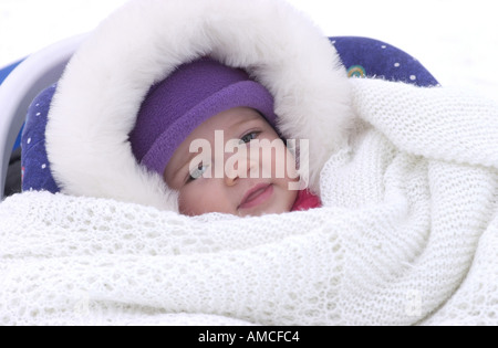 A baby swaddled in blankets and winter clothing in Winnipeg Manitoba Canada - Stock Photo