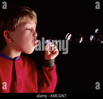 young Caucasian boy blowing bubbles - Stock Photo