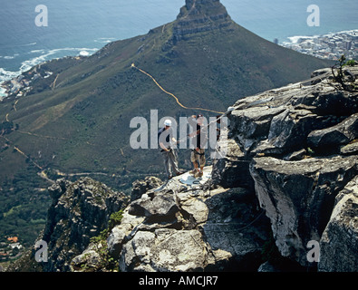 CAPE TOWN SOUTH AFRICA October Man preparing to abseil from the top of Table Mountain with Lion's Head in the background - Stock Photo