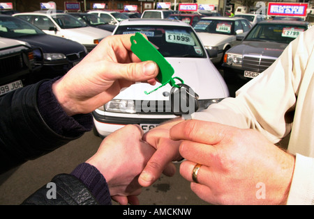A DEAL IS SEALED WITH A HANDSHAKE AT A USED CAR DEALERSHIP UK - Stock Photo