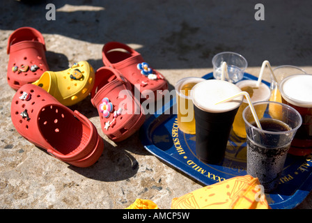 a pile of kids crocs shoes lie in disarray next to a pub tray with various drinks on concrete jetty in cornwall - Stock Photo