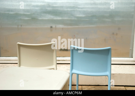 two empty chairs from rear looking through cloudy window over beach with surf in cornwall - Stock Photo