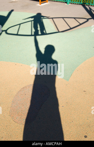 shadows of small child on climbing frame towering over shadow of adult on playground floor - Stock Photo