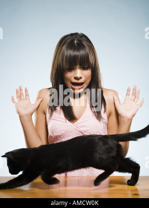 Woman with black kitten scared - Stock Photo