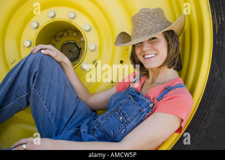 Woman reclining in tire with straw hat smiling - Stock Photo
