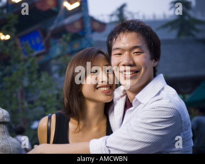 Couple embracing and smiling outdoors - Stock Photo