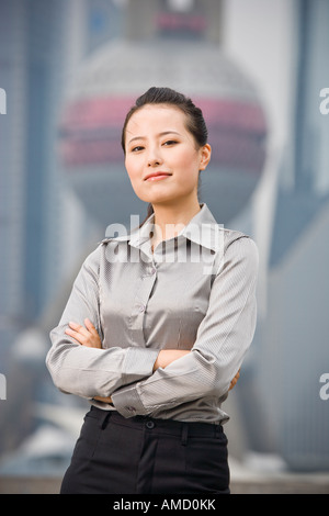 Businesswoman smiling outdoors with arms crossed - Stock Photo