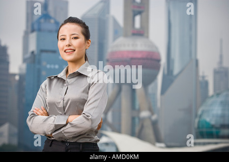 Businesswoman smiling outdoors with arms crossed and city skyline in background - Stock Photo