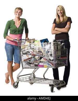 Two teenage girls with shopping cart filled with books and magazines - Stock Photo