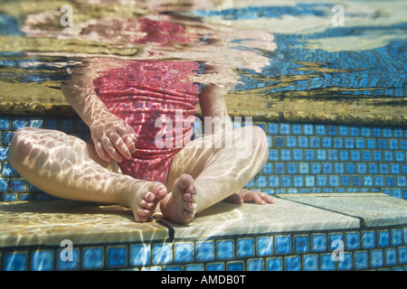 Girl sitting in pool waist down - Stock Photo