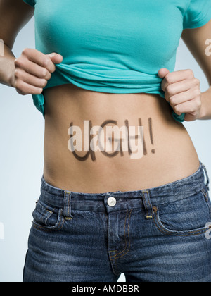Female Abdomen with UGH! written on it - Stock Photo