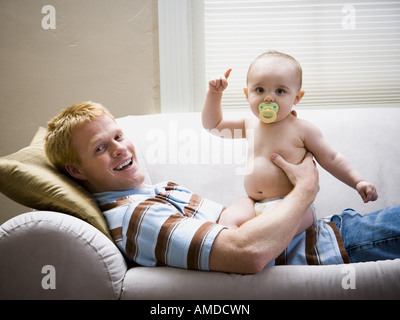 Man lying down on sofa with baby - Stock Photo