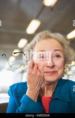 Senior woman holding glasses. - Stock Photo