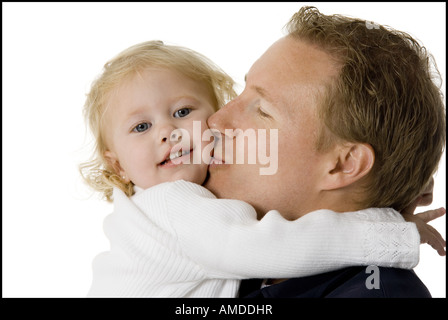 Man holding and kissing girl on cheek - Stock Photo