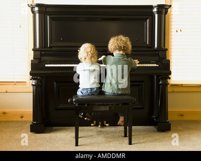 Rear view of two children sitting at upright piano