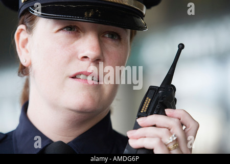 Close up of a female police officer talking in mobile phone. - Stock Photo
