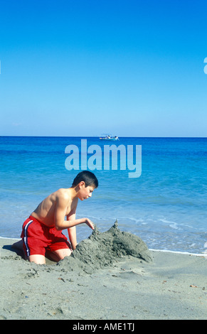a young boy building a sandcastle at the beach of Frangokastello at the Southern Coast of the Greek Island of Crete - Stock Photo