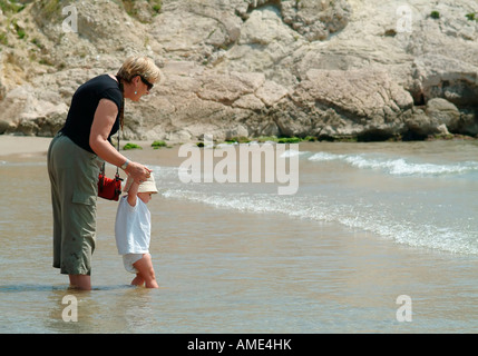 Happy grandmother and grandchild playing together and having fun on the beach in summer on a family holiday - Stock Photo