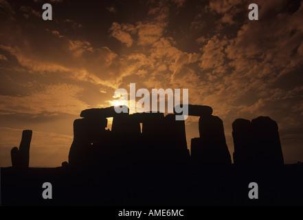 An orange sunset over the mystical stone circle of Stonehenge on Salisbury Plain - Stock Photo