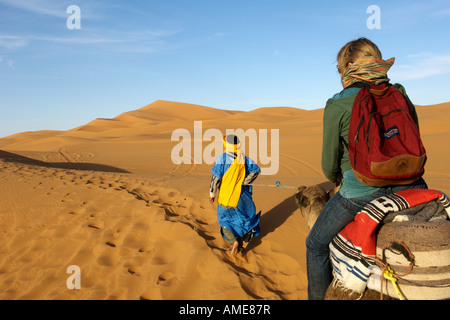 A berber man leads a woman on a camel through the dunes of Erg Chebbi on the periphery of the Sahara desert in eastern - Stock Photo