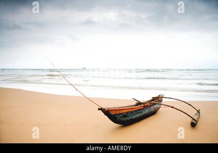 A fishermans outrigger on Bentota beach Sri Lanka during the rainy season - Stock Photo