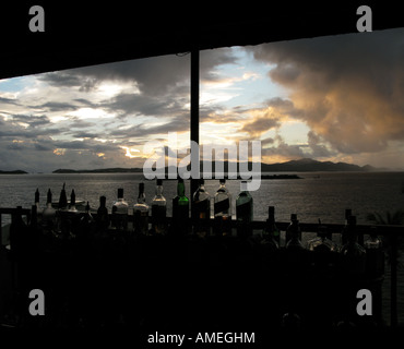 Overlooking Frank Bay from a cocktail bar, with St. Thomas in the distance, as a storm moves through at sunset. - Stock Photo