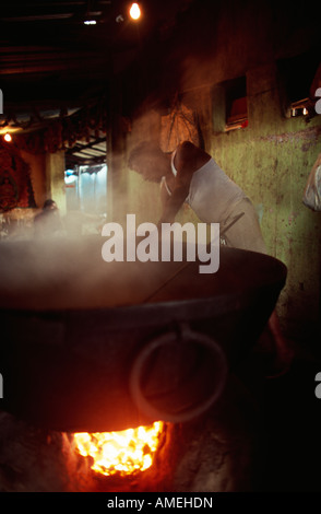 Man cooking in a large pot at the temple under the Howrah Bridge, Calcutta, India. - Stock Photo