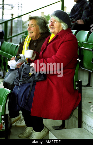 A COUPLE OF ELDERLY LADIES AT A FA CUP FOOTBALL MATCH FOREST GREEN ROVERS V TORQUAY UNITED UK - Stock Photo